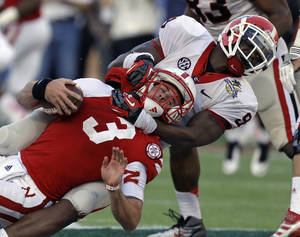 photo - Georgia linebacker Alec Ogletree (9) sacks Nebraska quarterback Taylor Martinez (3) on a fourth and nine play late in the fourth quarter of the Capital One Bowl NCAA college football game, Tuesday, Jan. 1, 2013, in Orlando, Fla. Georgia won 45-31. (AP Photo/John Raoux)
