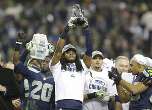 Photo - Seattle Seahawks' Richard Sherman holds up the George Halas Trophy after the NFL football NFC Championship game against the San Francisco 49ers Sunday, Jan. 19, 2014, in Seattle. The Seahawks won 23-17 to advance to Super Bowl XLVIII. (AP Photo/Elaine Thompson)