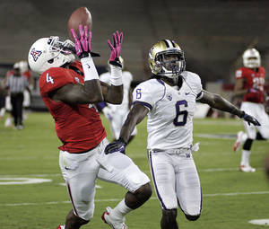 photo -   Arizona's Dan Buckner (4) catches the ball in front of Washington's Desmond Trufant (6) for a long gain during the first half of an NCAA college football game at Arizona Stadium in Tucson, Ariz., Saturday, Oct. 20, 2012. (AP Photo/Wily Low)
