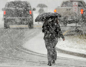 Photo - A Food City employee uses an umbrella to stay dry as she goes to work during a heavy snowfall Thursday afternoon in Bristol, Va. as shoppers make a last-minute trip to the grocery store.  (AP Photo/The Bristol Herald-Courier,Andre Teague )