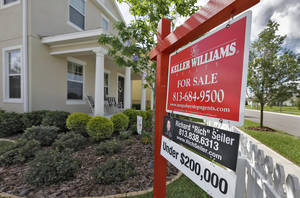 Photo - In this May 14, 2014 photo, a sign hangs in front of a new home for sale in Riverview, Fla.  Freddie Mac reports on average U.S. mortgage rates for this week on Thursday, June 19, 2014. (AP Photo/Chris O'Meara)