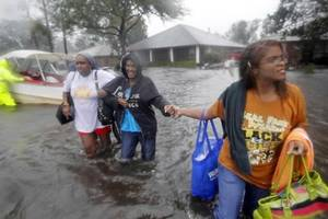 photo - St. John the Baptist Parish sheriff's deputies evacuate residents from the River Forest subdivision in LaPlace, La. as wind-driven tides flood the neighborhood Wednesday, Aug. 29, 2012. Isaac arrived exactly seven years after Hurricane Katrina and passed slightly to the west of New Orleans, where the city's fortified levee system easily handled the assault. (AP Photo/The Times-Picayune, Brett Duke)