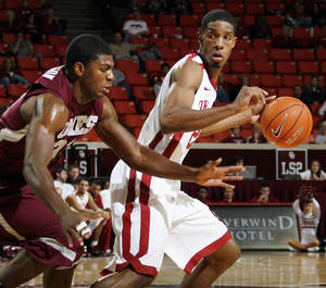 Photo - OU's Cameron Clark (21) dribbles away from Mark Robertson (31) of Maryland Eastern Shore during the men's college basketball game between Maryland Eastern Shore and Oklahoma at Lloyd Noble Center in Norman, Okla., Monday, January 3, 2011. Photo by Nate Billings, The Oklahoman