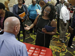 Photo - In this Thursday, June 12, 2014 photo, Marsha Lawson talks with a representative from CVS at the Cleveland Career Fair in Independence, Ohio. Optimism among chief executives of large U.S. companies has reached a two-year high, driven by greater optimism about hiring and sales. (AP Photo/Tony Dejak)