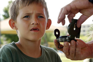 Photo -  Jasaic Riley, 8, is instructed in the use of a compass as Cub Scouts from Cleveland and McClain counties participate in day camp activities at the National Center for Educational Development. PHOTO BY STEVE SISNEY, THE OKLAHOMAN  <strong>STEVE SISNEY -   </strong>