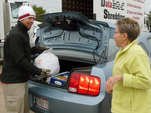 Photo - Jeff Moody, left, and Jayne Crumpley unload bags of items for the shredder at Saturday's Shred-a-Thon.