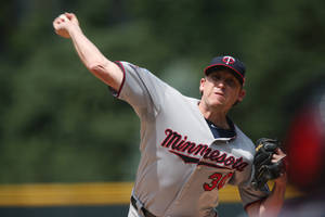 Photo - Minnesota Twins starting pitcher Kevin Correia works against the Colorado Rockies in the first inning of an interleague baseball game in Denver on Saturday, July 12, 2014. (AP Photo/David Zalubowski)