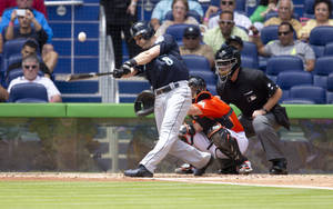 Photo - Seattle Mariners batter Willie Bloomquist hits a foul ball as Miami Marlins catcher Jeff Matthis (6) and umpire Ed Hickox watch during the third inning of a baseball game in Miami, Sunday, April 20,2014. (AP Photo/J Pat Carter)