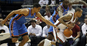 Photo - Oklahoma City Thunders' Thabo Sefolosha, left, knocks the ball away from Milwaukee Bucks' Monta Ellis, right, during the first half of an NBA basketball game Monday, April 9, 2012, in Milwaukee. (AP Photo/Jeffrey Phelps) ORG XMIT: WIJP104 <strong>JEFFREY PHELPS - AP</strong>