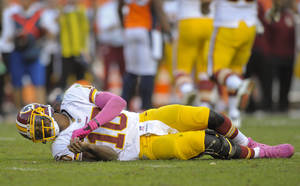 Photo - Washington Redskins quarterback Robert Griffin III (10) lays on the turf after a hit by the Denver Broncos in the fourth quarter of an NFL football game, Sunday, Oct. 27, 2013, in Denver. Griffin left the game after the play. (AP Photo/Jack Dempsey)