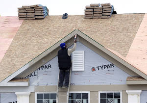 Photo - In this Monday, Nov. 11, 2013 photo, a worker caulks the peak of a new condominium complex under construction in Pepper Pike, Ohio. The Commerce Department releases new home sales for November on Tuesday, Dec. 24, 2013. (AP Photo/Tony Dejak)