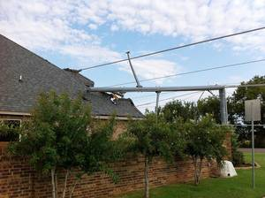 Photo - A utility pole fell onto the roof of a house at 5601 NW 164 Terrace during a thunderstorm Tuesday night. Photos by Robert Medley, The Oklahoman