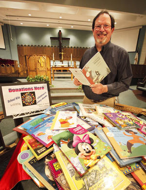 Photo - Rev. Ed Light of Grace United Methodist Church in Oklahoma City shows some of the books collected to give  Tulsa inmates to read to their children on tape. Photo By David McDaniel, The Oklahoman
