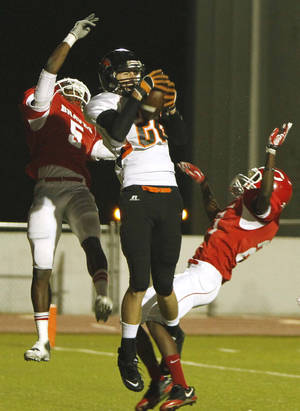 Photo - Tulsa Central No.5 Devanta Johnson, left, falls back as Coweta No.22 Hunter Raspberry, center, catches the ball to score a touchdown during the high school football game at Booker T. Washington High School in Tulsa, Okla., on Oct. 28,2011. JAMES GIBBARD/Tulsa World