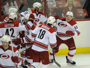 Photo - Carolina Hurricanes left wing Jeff Skinner (53) celebrates his game-winning goal with Eric Staal (12), Radek Dvorak(18), of the Czech Republic, Brett Sutter (42), John-Michael Liles(260 and others in the overtime period of an NHL hockey game against the Washington Capitals, Thursday, Jan. 2, 2014, in Washington. The Hurricanes won 4-3. (AP Photo/Nick Wass)