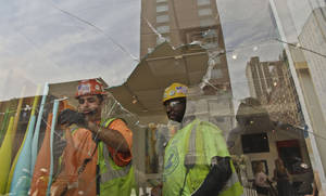 Photo -   Construction workers remove window display items near the shattered window of Kolb Art Gallery following damage from an intentional underground explosion on the Second Avenue subway project on East 72nd on Tuesday, Aug. 21, 2012. (AP Photo/Bebeto Matthews)