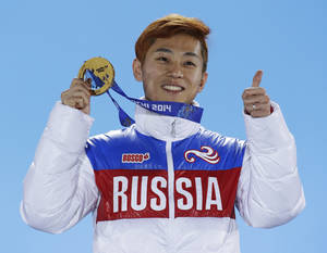 Photo - Men's 1,000-meter short track speedskating gold medalist Viktor Ahn of Russia gestures while holding his medal during the medals ceremony at the 2014 Winter Olympics, Saturday, Feb. 15, 2014, in Sochi, Russia. (AP Photo/David J. Phillip )
