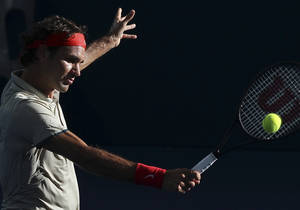 Photo - Roger Federer of Switzerland plays a shot in his semifinal match against Jeremy Chardy of France during the Brisbane International tennis tournament in Brisbane, Australia, Saturday, Jan. 4, 2014. (AP Photo/Tertius Pickard)