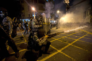 Photo - FILE - In this June 30, 2013 file photo, military police fire tear gas at protestors near Maracana stadium as Brazil and Spain play the final Confederations Cup soccer match in Rio de Janeiro, Brazil. Brazil has created a special riot force to help police control demonstrations expected during the 2014 World Cup, and authorities say they will not let protesters get too close to the stadiums. (AP Photo/Silvia Izquierdo, File)