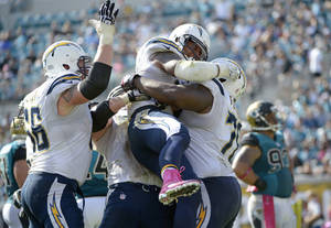 Photo - San Diego Chargers running back Ryan Mathews, center, is mobbed by teammates after scoring a touchdown on a 3-yard run against the Jacksonville Jaguars during the second half of an NFL football game in Jacksonville, Fla., Sunday, Oct. 20, 2013.(AP Photo/Phelan M. Ebenhack)
