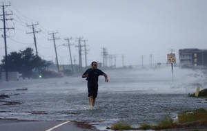 Photo - A man crosses a flooded Highway 64 as wind pushes water over the road as Hurricane Arthur passes through Nags Head, N.C., Friday, July 4, 2014. (AP Photo/Gerry Broome)