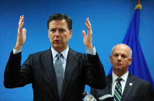Photo - In this photo from July 30, 2014, James Comey, Director of the Federal Bureau of Investigation, left, speaks to the media with U.S. attorney David J. Hickton at the FBI's Pittsburgh headquarters. Because of the Pittsburgh's cybersquad success, Comey said the FBI is rewarding the office with more manpower, allowing it to take on even more cyberthreats. (AP Photo/Post-Gazette-Michael Henninger)