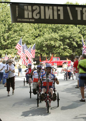 Photo - Disabled veterans cross the finish line on therapeutic trikes after parading around the Cox Convention Center on Saturday, July 14, 2012. The nonprofit organization AMBUCS awarded the trikes to disabled veterans and children during its national conference. By Paul Hellstern, The Oklahoman <strong>PAUL HELLSTERN - Oklahoman</strong>
