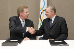 Photo - FILE - In this May 24, 2012 file photo, United States Olympic Committee chairman Larry Probst, left, and Olympic Committee President Jacques Rogge shake hands after signing an agreement between the IOC and the USOC at the SportAccord conference in Quebec City. Probst has been elected to the IOC, a big boost for the U.S. to regain influence on the Olympic stage. Probst made it onto the International Olympic Committee on Tuesday, Sept. 10, 2013, with 71 votes in favor and 20 against. (AP Photo/Mathieu Belanger, Pool, File)
