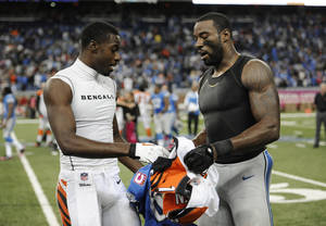 Photo - FILE--In this Oct. 20, 2013 file photo, Cincinnati Bengals wide receiver A.J. Green, left, and Detroit Lions wide receiver Calvin Johnson exchange jerseys after their NFL football game in Detroit.  Johnson takes the shirt off his back _ literally _ after some games to swap jerseys with an opponent. Johnson said he usually knows ahead of time when he's going to make a postgame trade, and doesn't plan to do it after Monday night's game against the Baltimore Ravens. (AP Photo/Jose Juarez, file)