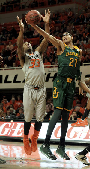 Photo - Baylor center Isaiah Austin (21) and Oklahoma State guard Marcus Smart reach for a rebound during the first half of an NCAA college basketball game in Stillwater, Okla., Saturday, Feb. 1, 2014. (AP Photo/Brody Schmidt)