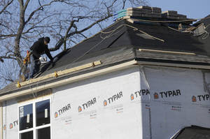 Photo - In this Friday, Dec. 27, 2013, photo, a construction worker builds a new home in Wilmette, Ill. The Commerce Department releases new home sales for December on  Monday, Jan. 27, 2014. (AP Photo/Nam Y. Huh)
