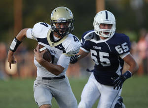 Photo - Heritage Hall's Connor MicGinnis (4) runs from Casady's Blake Gunn (65) during a game at Casady High School in The Village, Okla., Thursday, Aug. 30, 2012.  Photo by Garett Fisbeck, The Oklahoman