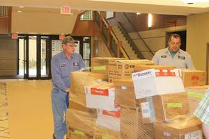 Photo - County road crewmen move pallets of boxes and furniture from one site to the next as the two-week transition into the new Rogers County Courthouse begins.  (Claremore Progress photo)
