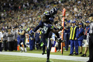 Photo - Seattle Seahawks' Derrick Coleman jumps on Seahawks' Marshawn Lynch (24) after Lynch scored his second touchdown of the second half of an NFL football game against the  San Francisco 49ers, Sunday, Sept. 15, 2013, in Seattle. (AP Photo/Elaine Thompson)