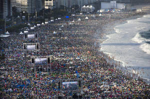 Photo - Pilgrims and residents gather on Copacabana beach before the arrival of Pope Francis for World Youth Day in Rio de Janeiro, Brazil, Saturday, July 27, 2013.  Francis will preside over an evening vigil service on Copacabana beach that is expected to draw more than 1 million young people. (AP Photo/Felipe Dana)