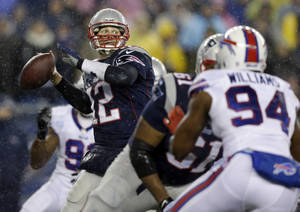 Photo - New England Patriots quarterback Tom Brady (12) passes against Buffalo Bills defensive end Mario Williams (94) in the first quarter of an NFL football game, Sunday, Dec. 29, 2013, in Foxborough, Mass. (AP Photo/Steven Senne)