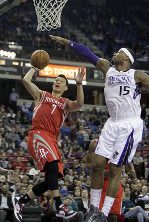 Photo - Houston Rockets guard Jeremy LIn, right, shoots against Sacramento Kings center DeMarcus Cousins during the first quarter of an NBA basketball game in Sacramento, Calif., Sunday, Feb. 10, 2013.(AP Photo/Rich Pedroncelli)