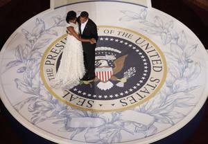 Photo - FILE - In this Jan. 20, 2009, file photo, President Barack Obama and first lady Michelle Obama dance at the Commander in Chief Inaugural Ball at the National Building Museum in Washington. Obama's second inauguration is shaping up as a high-energy celebration smaller than his first milestone swearing-in, yet still designed to mark his unprecedented role in American history with plenty of eye-catching glamour. A long list of celebrity performers will give the once-every-four years right of democratic passage the air of a star-studded concert, from the bunting-draped Capitol's west front of the Capitol, where Obama takes the oath Jan. 21, to the Washington Convention Center, which is expected to be packed with 40,000 ball-goers that evening. (AP Photo/Charles Dharapak, File)