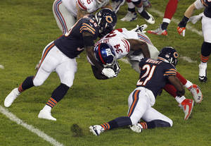 Photo - Chicago Bears linebacker D.J. Williams (58) and safety Major Wright (21) tackle New York Giants running back Brandon Jacobs (34) In the first half of an NFL football game, Thursday, Oct. 10, 2013, in Chicago. (AP Photo/Kiichiro Sato)