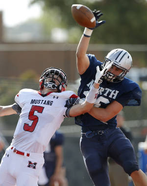 Photo - Edmond North's David Wright, at left, breaks up a pass intended for Mustang's Colton Hadlock during a high school football scrimmage at Mustang, Thursday, August 29, 2013. Photo by Bryan Terry, The Oklahoman