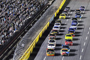 Photo - Kyle Busch, front right, and Ryan Newman, front left, lead the field to the start Saturday's NASCAR race at Charlotte Motor Speedway in Concord, N.C. AP Photo