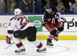 Photo - New York Rangers' Ryan Callahan, right, shoots past New Jersey Devils' Anton Volchenkov during the second period of an NHL hockey game on Sunday, April 21, 2013, in New York. (AP Photo/Seth Wenig)
