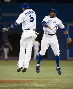 Photo -   Toronto Blue Jays shortstop Yunel Escobar, left, and left fielder Rajai Davis celebrate their win over the Minnesota Twins following a baseball game in Toronto on Tuesday, Oct. 2, 2012. (AP Photo/The Canadian Press, Nathan Denette)