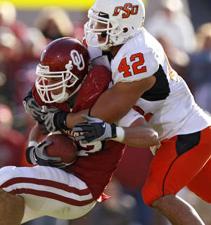 photo - OSU's Justin Gent (42) brings down Oklahoma's Trent Ratterree (47) last season. Photo by Chris Landsberger, The Oklahoman