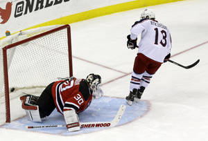 Photo - Columbus Blue Jackets right wing Cam Atkinson (13) scores a goal on New Jersey Devils goalie Martin Brodeur during a shootout in an NHL hockey game, Friday, Dec. 27, 2013, in Newark, N.J. The Blue Jackets won 2-1. (AP Photo/Julio Cortez)