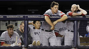 Photo -   Boston Red Sox players including Che-Husan Lin, third from left, Danny Valencia and Dustin Pedroia, far right, watch from the dugout during their 10-2 loss to the New York Yankees in their baseball game at Yankee Stadium in New York, Monday, Oct. 1, 2012. (AP Photo/Kathy Willens)