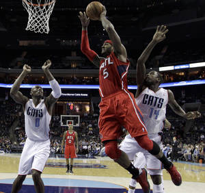 Photo - Atlanta Hawks' Josh Smith (5) drives to the basket past Charlotte Bobcats' Michael Kidd-Gilchrist (14) and Bismack Biyombo (0) during the first half of an NBA basketball game in Charlotte, N.C., Wednesday, Jan. 23, 2013. (AP Photo/Chuck Burton)