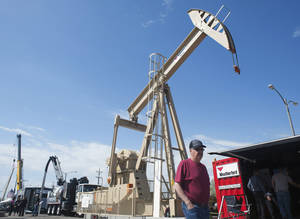 Photo - FILE - In this May 22, 2014 file photo, a visitor walks past a pumping jack on display in the outdoor exhibit area at the Bismarck Civic Center during the 22nd Williston Basin Petroleum Conference oil expo in Bismarck, N.D. The South Dakota School of Mines and Technology has plans to add a minor in petroleum systems. President Heather Wilson says the energy industry is growing in the region and many of the school's graduates work in that industry. (AP Photo/Kevin Cederstrom, File)