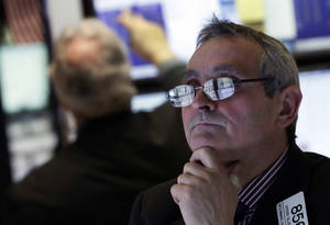 Photo - In this Wednesday, Jan. 23, 2013 photo, the screens of specialist Armin Silbersmith are reflected in his glasses as he works at his post on the floor of the New York Stock Exchange. Europe's stock markets were broadly higher Thursday Jan. 23, 2013 amid signs the continent's services and manufacturing slump was easing.  (AP Photo/Richard Drew)