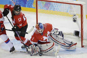 Photo - Goalkeeper Anna Prugova of Russia blocks a shot on the goal under pressure from Sara Benz of Switzerland during the 2014 Winter Olympics women's ice hockey game at Shayba Arena, Saturday, Feb. 15, 2014, in Sochi, Russia. (AP Photo/Matt Slocum)